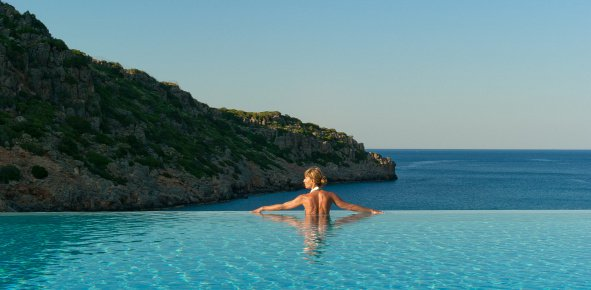 Woman in an infinity edge pool at a resort